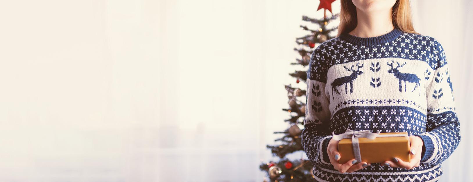 Frau mit Geschenk und Norwegerpulli vor Weihnachtsbaum