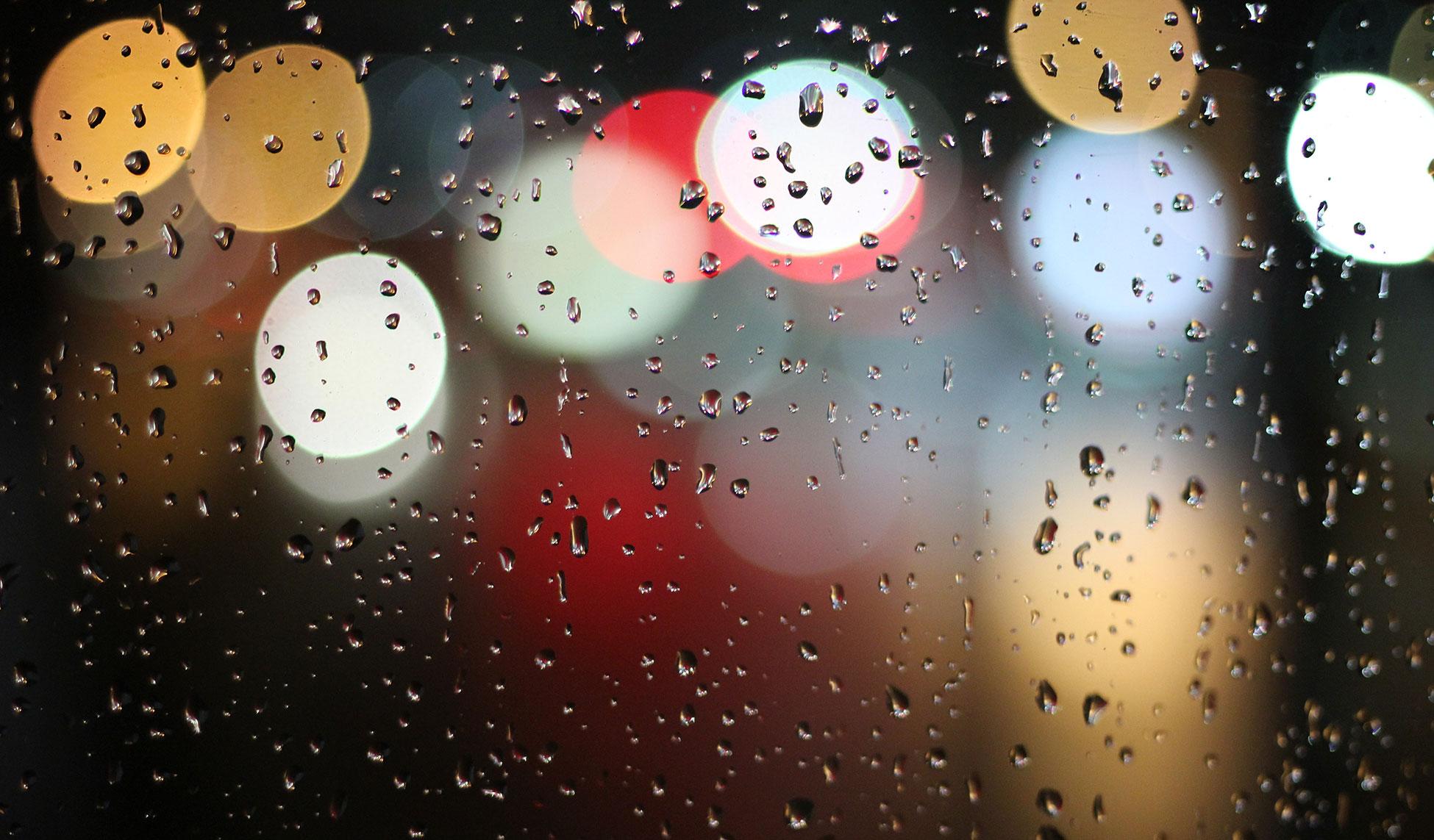 Wassertropfen auf Fensterscheibe, bunte Lichter