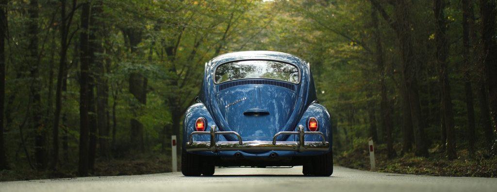 Blauer VW Käfer auf einem Waldweg