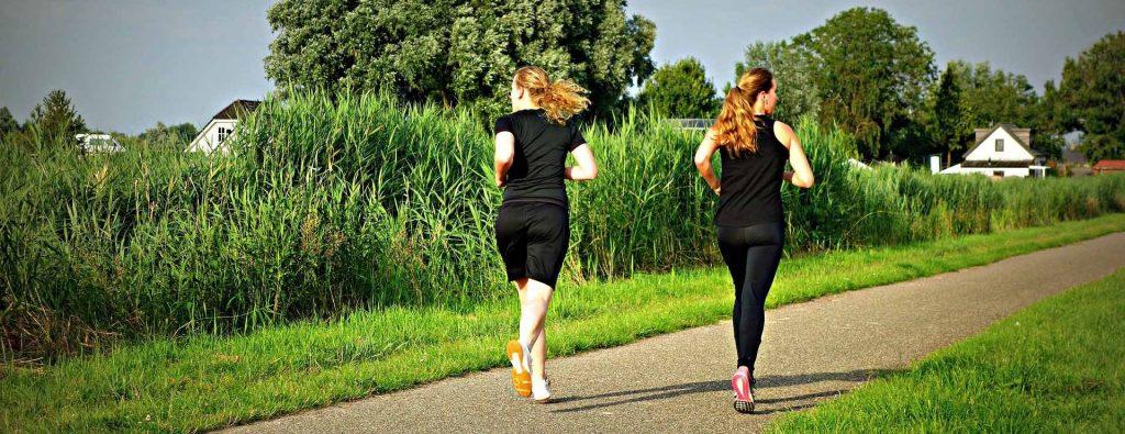 Zwei Damen joggen auf einem Feldweg